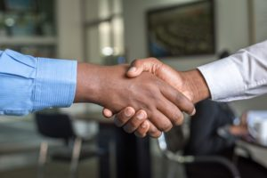a temp to perm employee shakes the hand of their employer